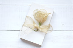 Blank papers to write letters. Tied with a raffia ribbon and decorated with an artificial flower on an old white wooden table Stock Image