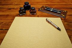 Blank parchment paper surrounded with the fountain pens and the inks. Blank parchment paper on the wooden table surrounded with the fountain pens and the inks royalty free stock image