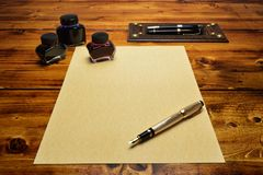 Blank parchment paper surrounded with the fountain pens and the inks. Blank parchment paper on the wooden table surrounded with the fountain pens and the inks stock image
