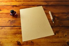 Blank parchment paper on the wooden table with the gold fountain pen and the ink around the paper. stock photo