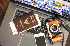 Blank passports and cameras with money on Laptop. Royalty Free Stock Image