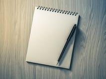 blank penna för anmärkningspapper på wood bakgrund Arkivfoto