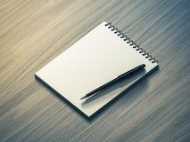 blank penna för anmärkningspapper på wood bakgrund Arkivbild