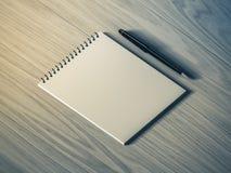 blank penna för anmärkningspapper på wood bakgrund Royaltyfria Foton