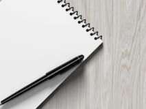 blank penna för anmärkningspapper på wood bakgrund Fotografering för Bildbyråer