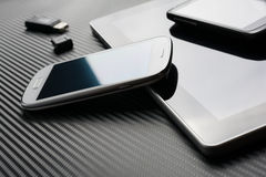 Blank Phones With Reflection Lying And Leaning On Business Tablet Beside An USB Flash Drive Above A Carbon Background Stock Photo