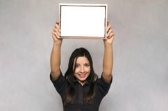Blank photo frame border in woman hands. Diploma. Certificate. Special offer. Young business woman in strict dress holding in hands empty blank photo frame Stock Photography
