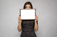 Blank photo frame border in woman hands. Diploma. Certificate. Special offer. Young business woman looks out from blank photo frame holding in her hands Royalty Free Stock Photo