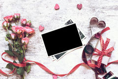 Blank photo frame with bouquet of pink roses, gift box, wooden h Royalty Free Stock Image