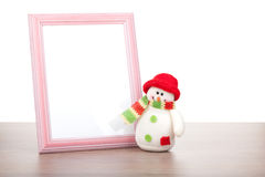 Blank photo frame and christmas snowman on wooden table Royalty Free Stock Images