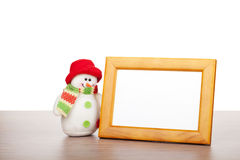Blank photo frame and christmas snowman on wooden table Royalty Free Stock Image