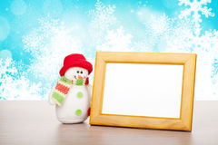 Blank photo frame and christmas snowman on wooden table Stock Photos