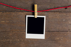 Blank photo frame with clothesline hanging on wood Royalty Free Stock Photography