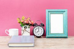 Blank photo frame on desk space. With notebook on pink background stock images