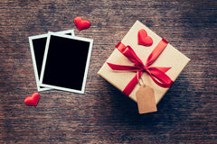 Blank photo frame and gift box with red heart on wood background Royalty Free Stock Image