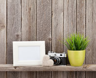Blank photo frame, heart, camera and plant. Blank photo frame, heart gift, camera and plant on shelf in front of wooden wall royalty free stock photos