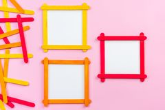 Blank photo frame made of popsicle sticks. Blank photo frame made of color popsicle wood sticks on pink background royalty free stock image