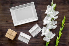 Blank photo frame near flower gladiolus on dark wooden background top view mockup Stock Photo