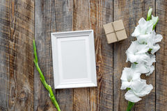 Blank photo frame near flower gladiolus on rustic wooden background top view mockup Royalty Free Stock Photo