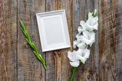 Blank photo frame near flower gladiolus on rustic wooden background top view mockup copyspace Stock Image