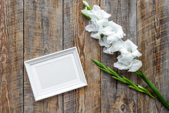 Blank photo frame near flower gladiolus on rustic wooden background top view mockup copyspace Royalty Free Stock Images