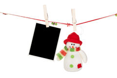 Blank photo frame and snowman hanging on the clothesline Stock Photography