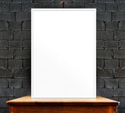 blank photo frame on wood table at black brick wall,perspective Royalty Free Stock Images