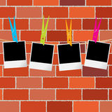 Blank photo frames with clothes pegs on rope over brick wall Royalty Free Stock Images