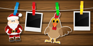 Blank photo frames, rooster and Santa Claus on a clothesline. Royalty Free Stock Photos