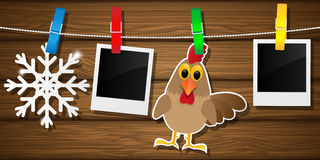 Blank photo frames, rooster and snowflake on a clothesline. Vector illustration. Royalty Free Stock Images