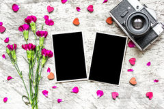Blank photo frames, vintage retro camera and purple carnation flowers. With wooden hearts and petals over white rustic wooden background stock photo