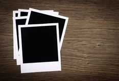 Blank photo frames on wooden background Stock Photos
