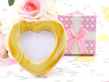 Blank photo heart wood frame with pink roses and gift box on sweet flower Royalty Free Stock Image