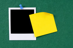 Polaroid frame yellow post it sticky note copy space. Polaroid : Blank photo print with sticky note pinned to a green felt notice board Royalty Free Stock Photos