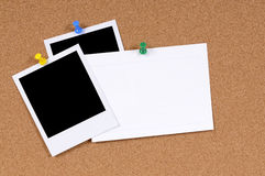Polaroid frames blank index card copy space. Blank polaroid photo prints with office index card pinned to a cork bulletin board Stock Image