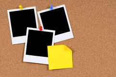 Polaroid photo frames sticky note cork background copy space. Blank polaroid photo prints with yellow sticky note pinned to a cork bulletin board stock photo