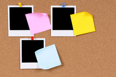 Blank polaroid photo prints with post it style sticky notes pinned to cork board, copy space Stock Photo