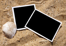 Blank Photograph Memory Pictures on Sand. Two blank, black photograph pictures are in the sand and there is a sea shell next to them. Use it for a summer Royalty Free Stock Photography