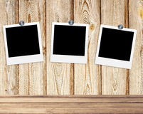 Blank photos on clips on wooden background Royalty Free Stock Photography