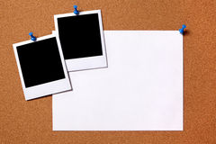 Polaroid photo frames paper poster pushpin cork board copy space. Blank photo prints and plain paper poster pinned to a cork notice board.  Space for copy Royalty Free Stock Image