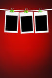 Blank photos on red background. Blank photos hanging on rope, red background Royalty Free Stock Image