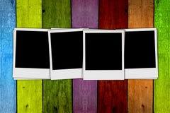 Blank Photos on Wood Background. Four blank photos on a multicolored wood background Royalty Free Stock Photography