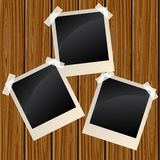 Blank photos on a wooden wall. Blank instant photo frames on a wooden wall Royalty Free Stock Photos