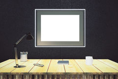 Blank picture frame on black wall with wooden table with lamp an. D diary, mock up Royalty Free Stock Photos