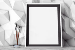 Blank Picture Frame with Brushes in front of Low Polygon Decorat Stock Photos