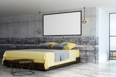 Blank picture frame on concrete wall. Wooden bed with yellow blanket and blank white poster with picture frame on concrete wall in loft bedroom. 3D render stock illustration