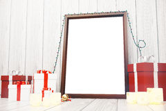 Blank picture frame with gift boxes and candlesticks on white wo. Oden floor, mock up Royalty Free Stock Image