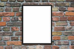 Blank picture frame hanging on brick wall - framed poster mock-up with stone wall background.  royalty free stock photo