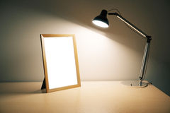 Blank picture frame with lamp on wooden table Royalty Free Stock Image