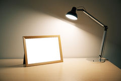 Blank picture frame with lamp on wooden table Stock Images